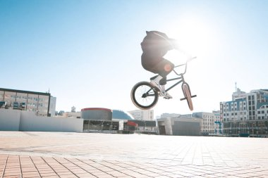 BMX freestyle. BMX cyclist makes complex tricks on a bike. Young man makes spectacular stunts against the background of the city square.