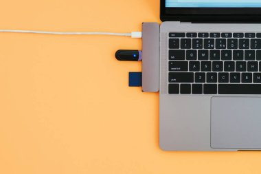 Modern laptop, USB Type-C adapter with a flash and charging on orange background. Technology concept. Copyspace. Adapter for new standards.