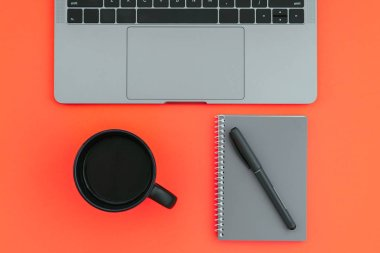 Workplace with a colored background. Laptop, a cup of coffee, a notepad with a pen isolated on a red background. Flat lay