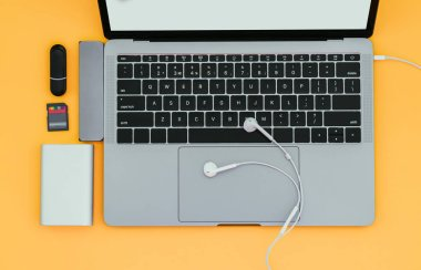 Notebook with USB Type-C adapter, flash drives, headphones and Power Bank isolated on a yellow background. Gadgets for a modern notebook.