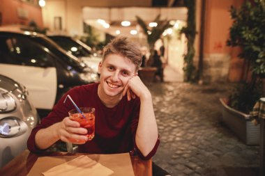 Portrait of a smiling young man who sits in the evening restaurant with a glass of alcohol in his hands,looks camera.Happy young man spends time at night in a cozy restaurant on the terrace