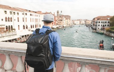 Tourist travels to Europe, a photo from Venice. The back of a young tourist with a black backpack stands on the bridge and looks at the beautiful canal and architecture.