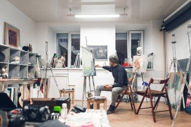 """Картина, постер, плакат, фотообои """"художник сидит на стуле в уютной студии и работает над картиной, рисуя картины маслом. художник работает в домашней студии живописи. живопись как хобби и работа. интерьер студии . абстракция все"""", артикул 235701856"""