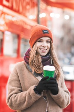 Beautiful woman in warm clothes standing on a winter street with a paper cup of coffee, on a bright street background,looking into the camera and smiling. Girl with a cup of coffee in hand on the walk