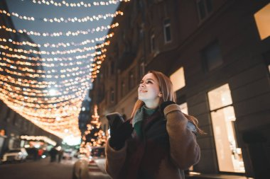 Satisfied girl stands in the street with Christmas lights, holds a smartphone in her hand, looks up and smiles. Joyful girl uses smartphone and smiles. Christmas portrait. stock vector