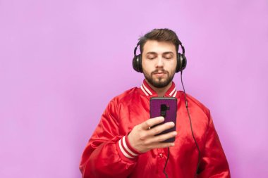 Portrait of a bearded man in the headphones standing against the background of a pink wall with a smartphone in his hand, looking focused on the screen, wearing a red jacket. Isolated.