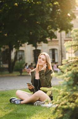 Attractive girl sitting on lawn in university park with books and smartphone in her hand, listening to music in headphones with her eyes closed and a smile on her face. Vertical