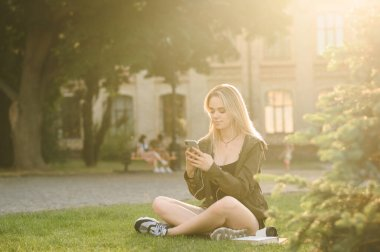 Attractive girl sits at sunset in a campus campus with books, uses a smartphone and listens to music in headphones. Pretty lady student uses smartphone on break on university background.