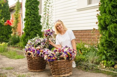 Positive woman sitting in the yard at the cottage with baskets of flowers and posing for the camera with a smile on his face.Blonde woman sitting near the house with baskets of beautiful dried flowers