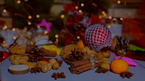 Weihnachts-Dekor auf dem Tisch - Spielzeug, Mandarinen, Cookies, Gewürzen und den blinkenden Kranz