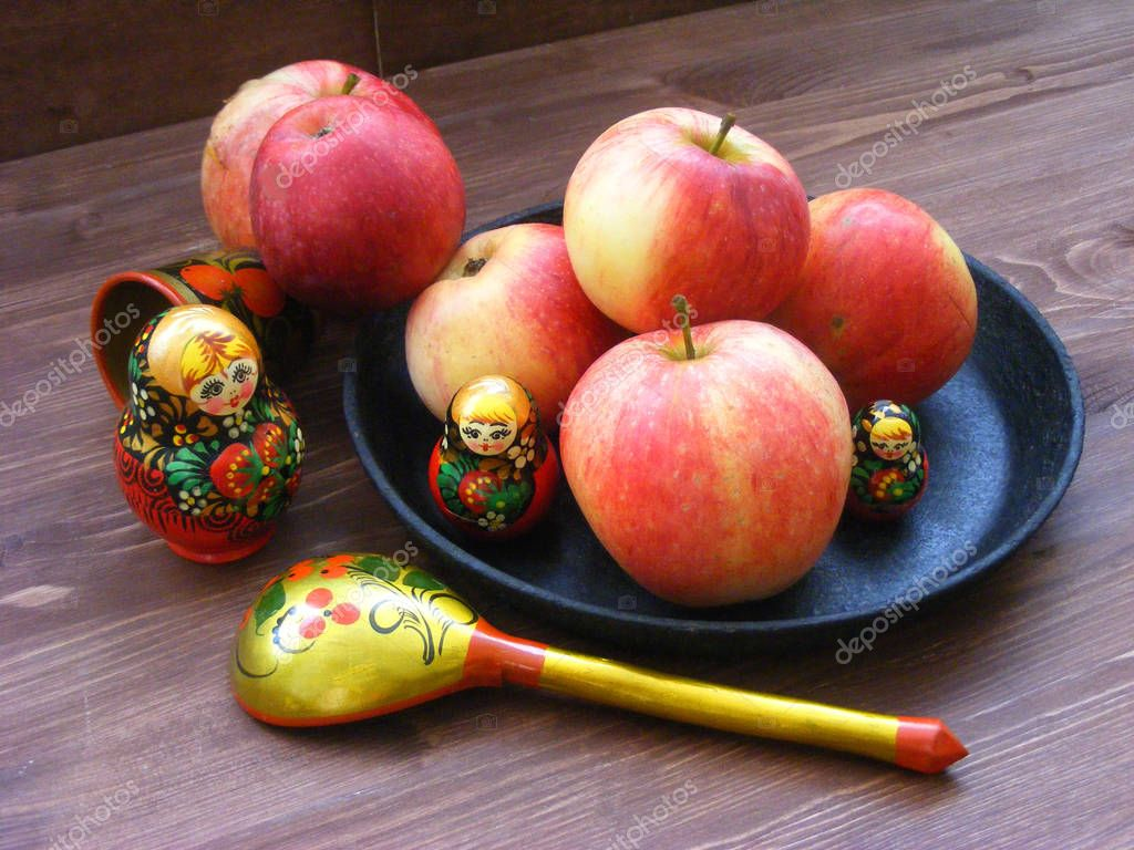 composition of red and yellow apples on black cast iron plate with traditional russian nesting dolls matrioshka and painted spoon on brown wooden table