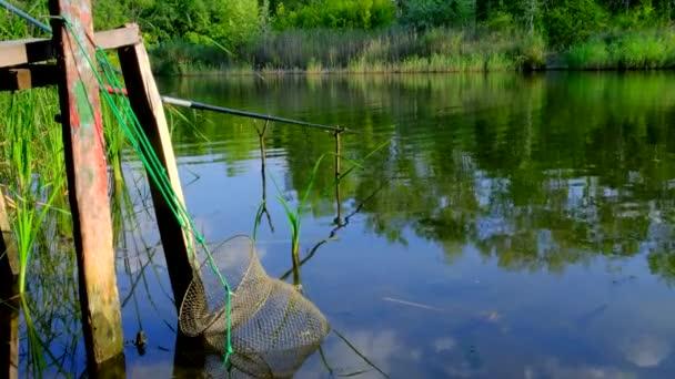 Rybářská prut a plout v řece v letním dni. Rybářské náčiní s cívkou a klecí pro chycené ryby. Pozadí přírody