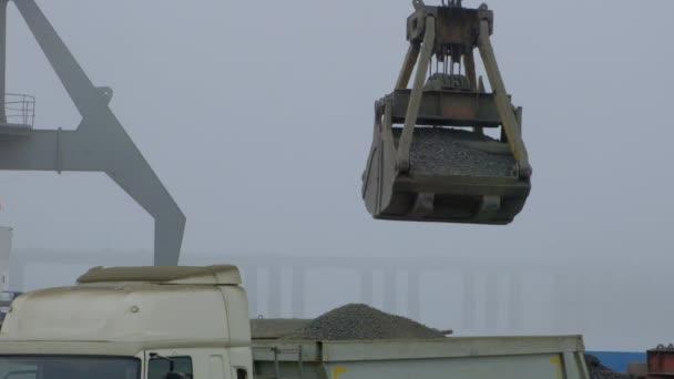 Greiferkran entlädt Zementklinker im Binnenhafen von Schiff zu LKW. Barge Lieferung staubiger Massengüter. Portalkran Entladung und Verladung im Hafen, im Freien. Logistik. Handel, Seefahrt