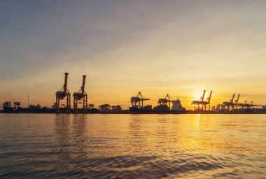 Container cargo ship in the export and import business and logistics international goods in urban city. Shipping cargo to the harbor by crane at sunset.