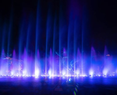 Colorful lights with blurry fountain, water show on black background in city at night