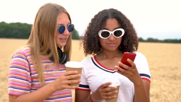 33b1ac2a0232 Slow motion tracking video clip of pretty blonde girl and mixed race  teenager young women wearing sunglasses drinking coffee and using mobile  cell smart ...