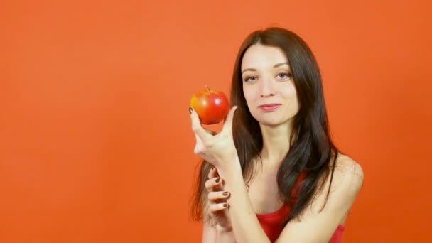 Mladá krásná žena s dokonalou pletí jíst červené jablko na oranžové pozadí. Pojem dieta. Zdravé jídlo