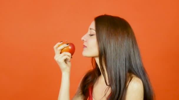 Usmívající se žena s zdravé zuby jíst červené jablko na oranžové pozadí ve studiu. Pojem dieta. Vegetariánské jídlo