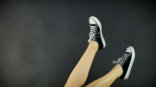 Ženské nohy v klasické černé a bílé tenisky. Nohy jsou vyvolány nahoru a houpat ze strany na stranu. Šedé, černé pozadí. Klasické boty, retro styl. Zdravý životní styl