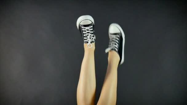 Frauenbeine in klassischen schwarz-weißen Turnschuhen. Die Beine sind nach oben gerichtet und baumeln von Seite zu Seite. schwarzer Hintergrund. klassische Schuhe. Gesunder Lebensstil