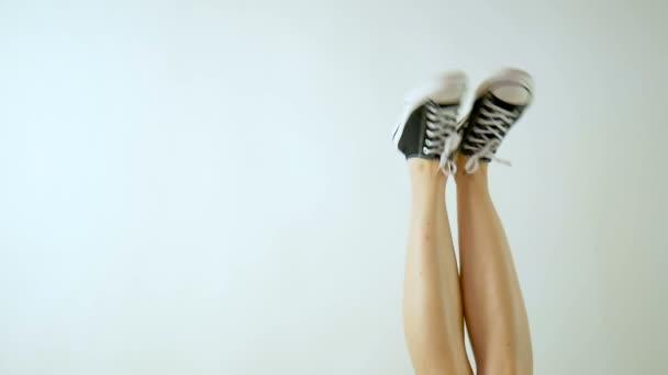 Frauenbeine in klassischen schwarz-weißen Turnschuhen. Die Beine sind nach oben gerichtet und baumeln von Seite zu Seite. grauer Hintergrund. klassische Schuhe. Gesunder Lebensstil