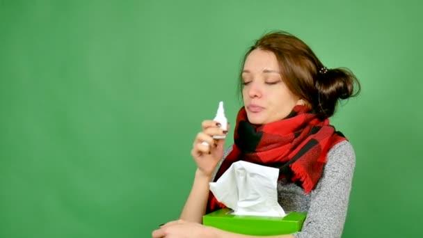 Portrét atraktivní bruneta s chřipkou. Dívka má nachlazení, horečky, krk je zabalena v šálu. Pocity nos kapkami do nosu