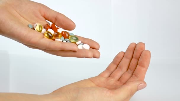 Multicolored vitamins and tablets in the hands of the girl. Pharmacy, healthy eating. Pour from hand to hand