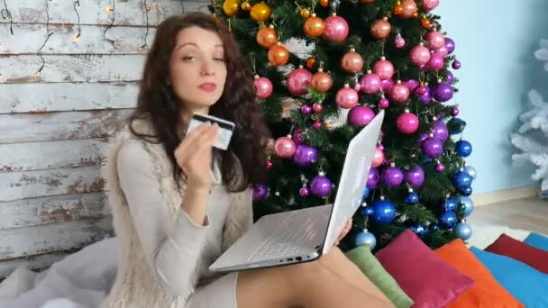 lockige Brünette mit Kreditkarte für den Online-Einkauf. Käuferinnen kaufen Weihnachtsgeschenk im Internet. Neujahr Urlaub fröhliche Weihnachtsfeier.