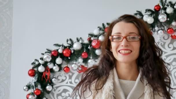 Portrét šťastné bruneta dívka, která nosí brýle a teplý svetr na pozadí vánoční výzdobou. Kudrnatá dívka smích