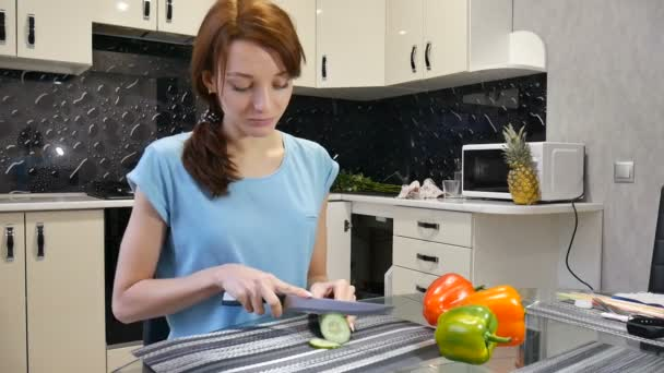 junge Frau schneidet frische grüne Gurken mit einem Messer in der Küche. gesunder Lebensstil und Ernährungskonzept