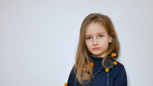 Krásná holčička s dlouhými blonďatými vlasy a velké modré oči nošení banda žluté vánoční osvětlení na bílém pozadí