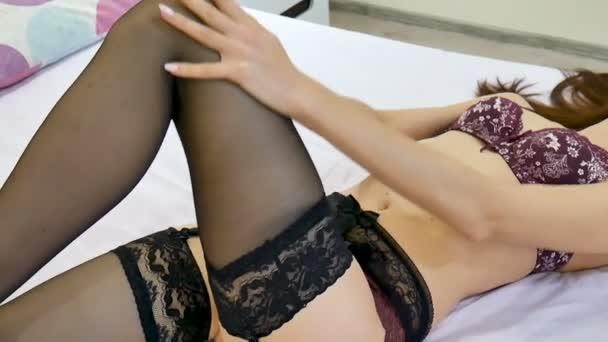 sexy junge Frau in dunkelroter Spitzenunterwäsche und schwarzen Strümpfen auf einem Bett liegend