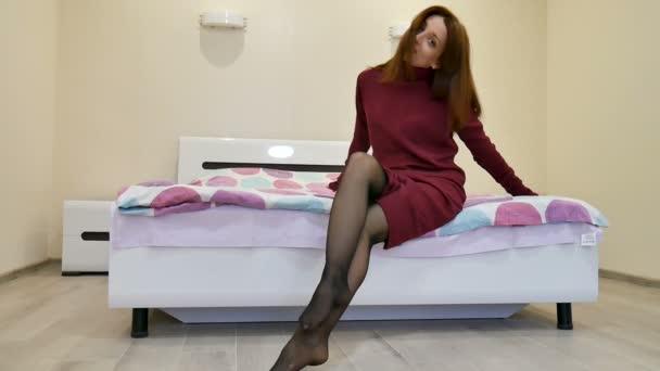 Atraktivní žena v neformálním tmavě červených šatech flirtuje s divákem zatímco sedí na posteli doma