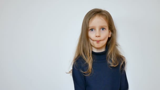 Close up portrait of cute girl with long blonde hair and big blue eyes grimacing while posing at studio