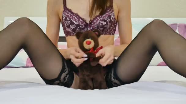 provokante junge sexy Frau in Dessous hält in schwarzen Strümpfen einen Stoffteddy zwischen ihren Beinen