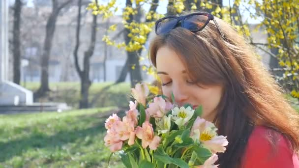 Emotional young woman with sunglasses standing outside with a big bouquet of colorful flowers and smiling during early spring near yellow bush on the background