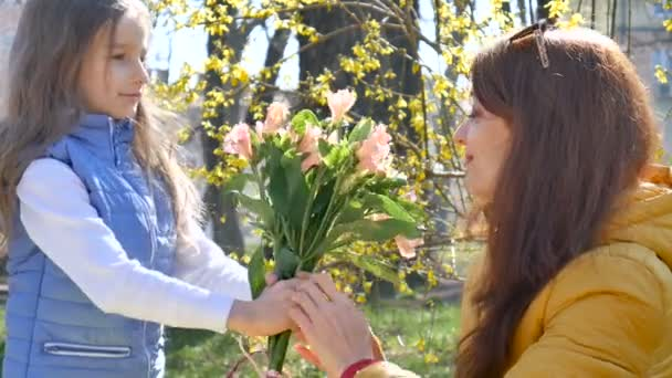 Happy mothers day. Child daughter congratulates mom and gives her a flowers. Mum and girl smiling and hugging. Family holiday and togetherness.