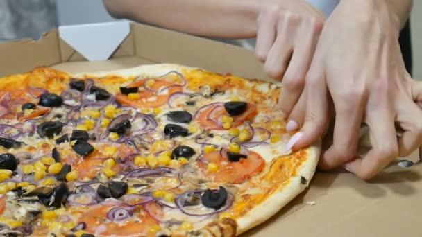 Zavřít video dívky ručně si vzít kousek pizzy s houbami, sýrem, kukuřicí, olivami, červenými cibulovkami a rajčaty z lepenkové krabice