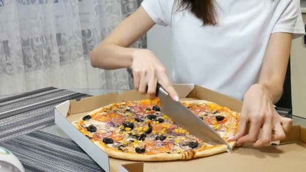 Žena krájí horkou pizzu s houbami, sýrem, kukuřicí, olivami, červenými cibulovými kroužky a rajčaty v kartonové krabici s nožem.