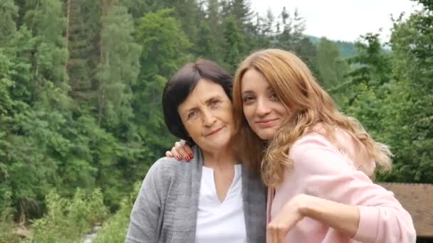 Outdoor close up portrait of smiling happy caucasian senior mother with her adult daughter hugging and looking at the camera