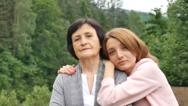 Portré egy komoly anya és felnőtt lánya a háttérben a hegyek a nyáron. Boldog öregség, anyák napja, lánya utazik egy idős anya