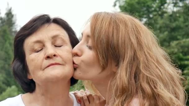 Ve venkovním prostoru zblízka portrét usmívající se šťastné kavkazské matky se svou dospělou dcerou, která se dívá na kameru. Dospělá dcera líbá matku, matky den