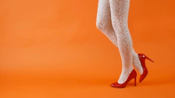 Sexy gambe lunghe su tacchi alti scarpe rosse e calze a rete bianche su sfondo arancione. Stile retrò