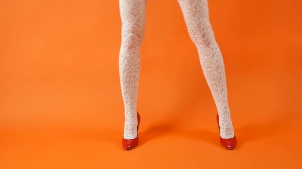 Sexy female legs in red high heel and fishnet stockings posing over orange background in studio. Retro style