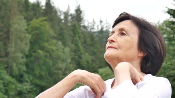 Seniorin macht Dehnübung für die Oberarme draußen über Wald- und Gebirgslandschaft
