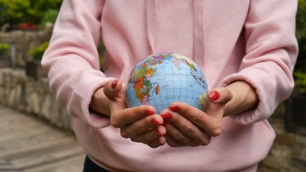 Female hands with red manicure taking a small globe with geografical names in Ukrainian cyrillic letters on it. Human responsibility concept.
