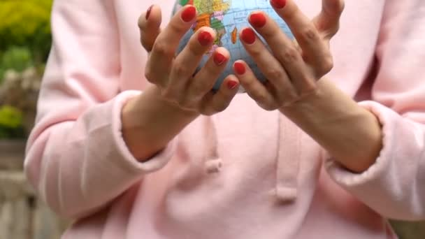 Female hands with red manicure giving a small globe with geografical names in Ukrainian cyrillic letters on it. Human responsibility concept