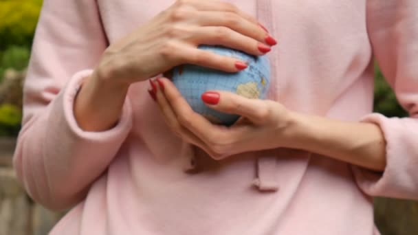 Young woman in casual clothes with red manicure giving a small globe with geografical names in Ukrainian cyrillic letters on it. Human responsibility concept