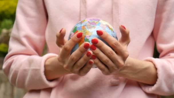 Female hands with red manicure giving a small globe with geografical names in Ukrainian cyrillic letters on it. Ecological problems concept