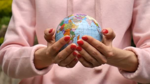 Close up video of female hands with red manicure giving a small globe with geografical names in Ukrainian cyrillic letters on it. Eco friendly lifstyle concept